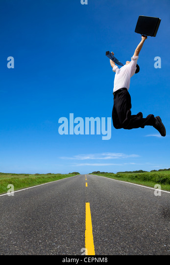 success business man jumping on the road - Stock Image