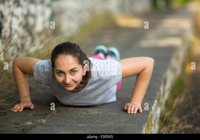 Young sports girl doing push-ups during the warm-up before Jogging in the Park. Healthy lifestyle. - Stock Image