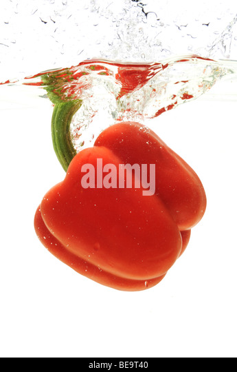 Red pepper dropped in the water isolated against a white background - Stock-Bilder