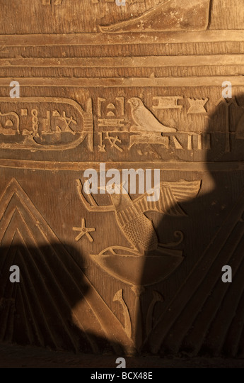 Egypt Kom Ombo temple shadows of two people viewing hieroglphic reliefs - Stock Image