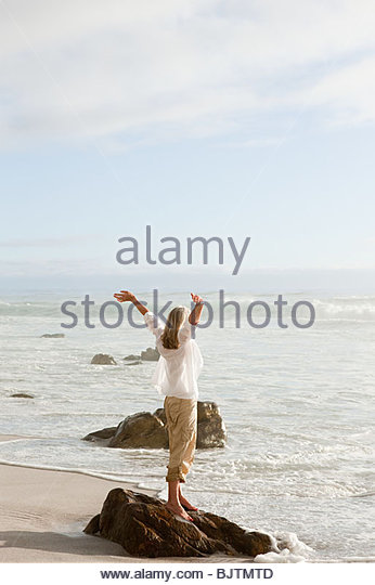 Woman standing on rock by the sea - Stock Image