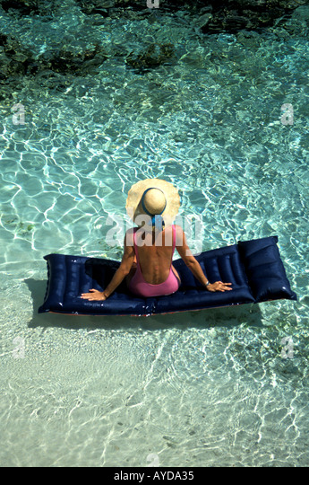 Tropical Beach Woman straw hat on Raft clear water with underwater corals clearly visible from above looking down - Stock Image