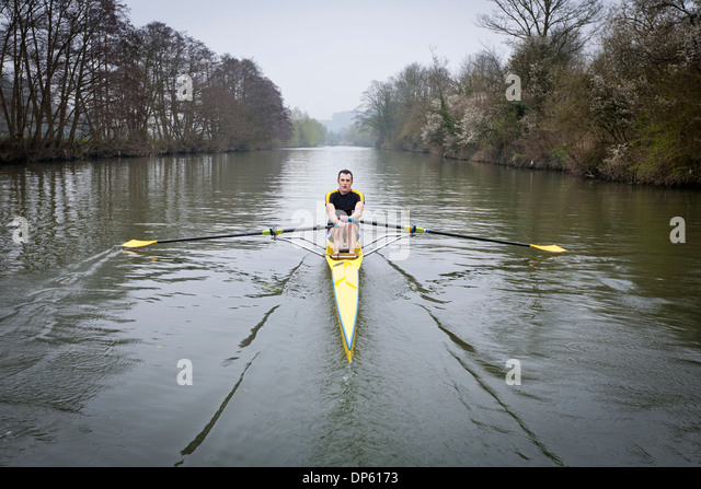 One man in a single scull rowing boat on the river Avon in Bath, UK. - Stock Image