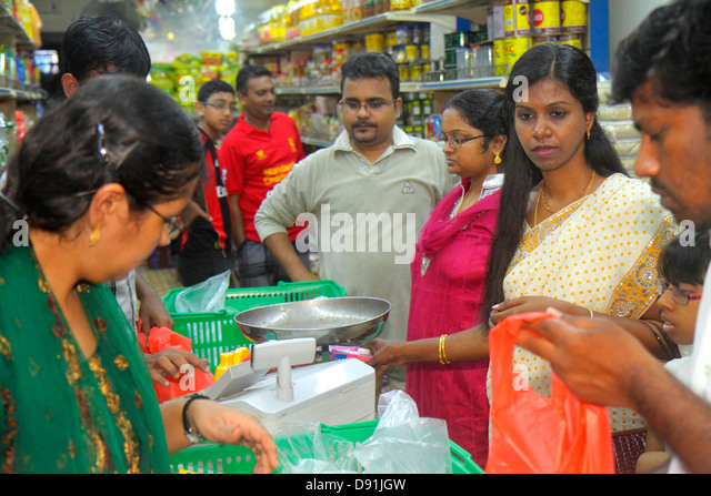 Singapore Little India Serangoon Road Asian man woman shopping grocery store supermarket food line queue check-out - Stock Image