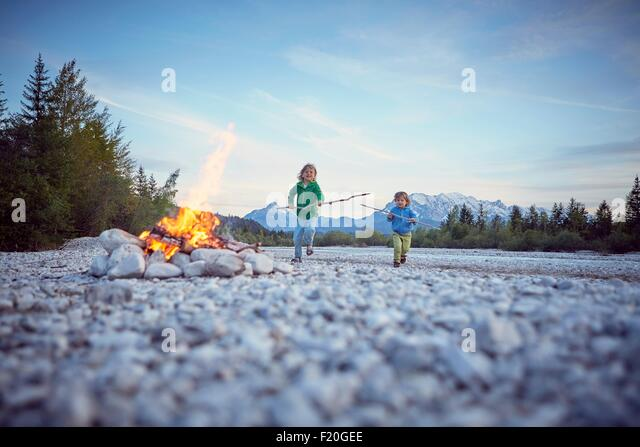 Front view of boys running to campfire holding sticks, Wallgau, Bavaria, Germany - Stock Image