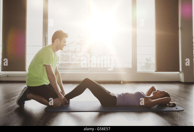 woman with personal trainer doing sit ups in gym - Stock-Bilder