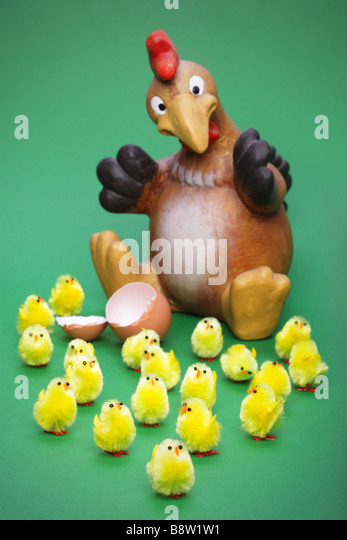 Lots of little toy chicks and a shocked parent focus is on the little guy at the front - Stock Image