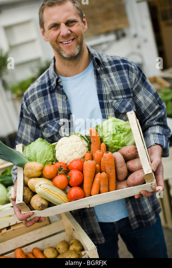 Man carrying a box full of vegetables. - Stock Image