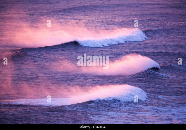 waves breaking on the beach looking west from Dyrhólaey at dusk, Iceland - Stock Image