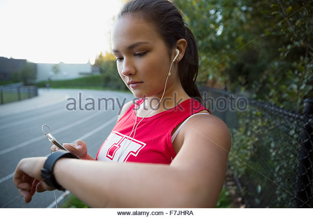High school athlete listening music checking wristwatch - Stock Image
