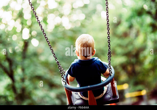 Playful child on swing outdoors, shot from behind - Stock Image