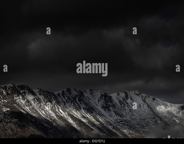 An ominous sky with some sunlight breaking through over a mountain range - Stock Image