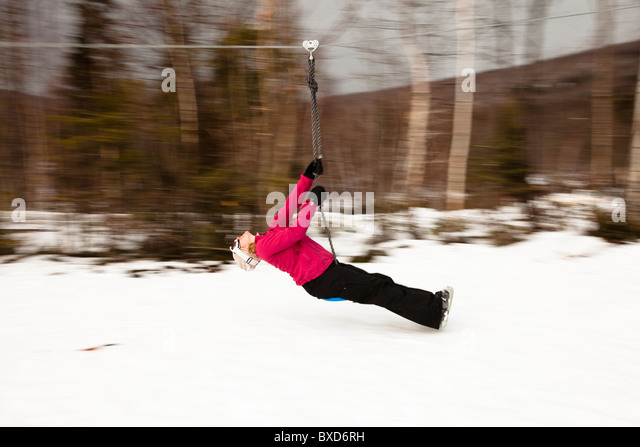 A woman plays on a zip line in Bretton Woods, New Hampshire. Blurred motion. - Stock Image