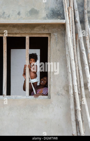 Young Indian baby girl standing in a window frame in a rural indian village. Andhra Pradesh, India - Stock Image