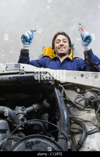 Auto mechanic repairing a car in a garage - Stock Image