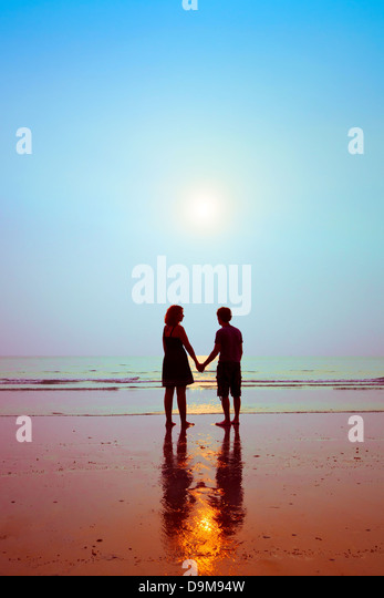 honeymoon, silhouettes of loving couple on the beach - Stock Image