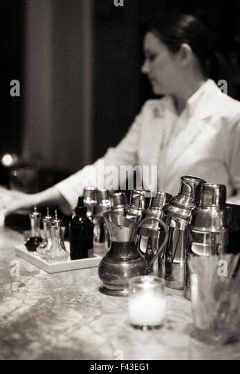Young woman mixing a cocktail at Piora Restaurant in Manhattan's West Village. Black and white image. - Stock Image
