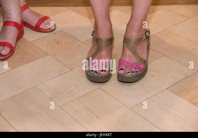 Women's sandles painted with pink lettering spelling out No Brexit - Stock Image