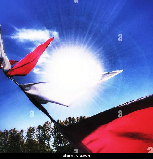 Red and white pennants flying in the wind. - Stock Image