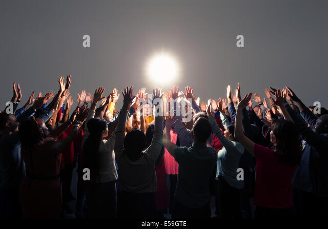 Diverse crowd with arms raised around bright light - Stock Image