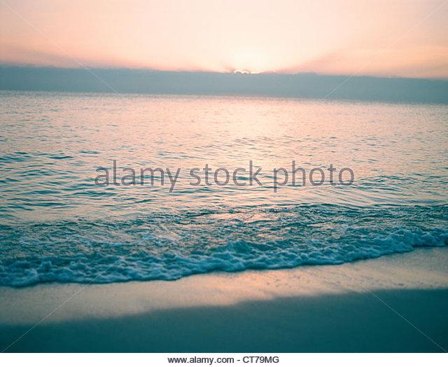 Sunrise over calm sea - Stock Image