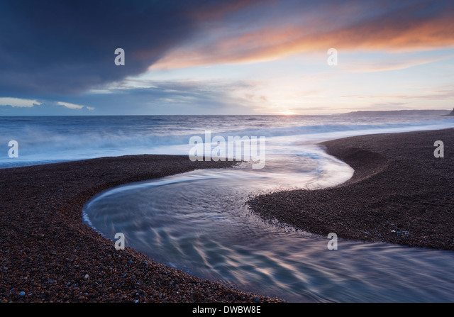 River Winniford flowing into the sea at Seatown Beach. Jurassic Coast World Heritage Site. Dorset. UK. - Stock Image
