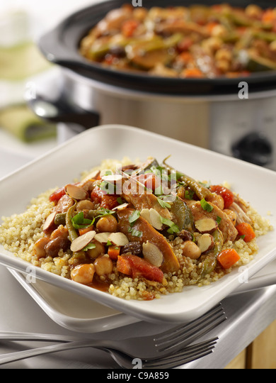 Moroccan chicken stew served over grains in a kitchen setting with a crock pot in the background - Stock Image