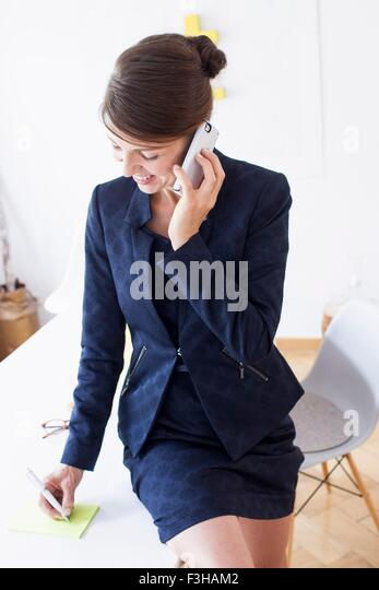 Mature woman wearing business attire using smartphone looking down smiling - Stock Image