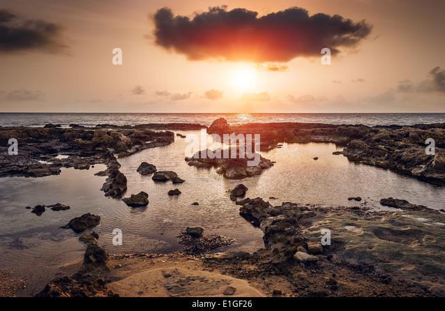 sunset over the sea and rocky coast in Mahdia, Tunisia - Stock Image