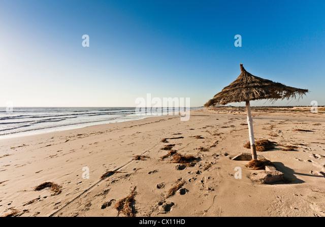 Parasol on beach on island of Djerba, Tunisia - Stock Image