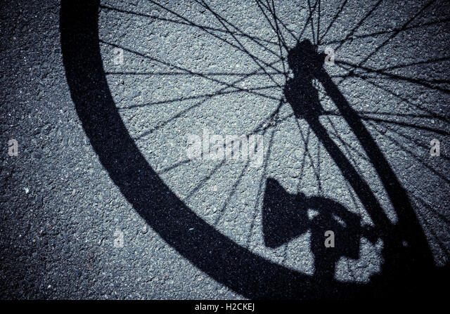 Shadow on street of wheel of a bicycle - Stock-Bilder