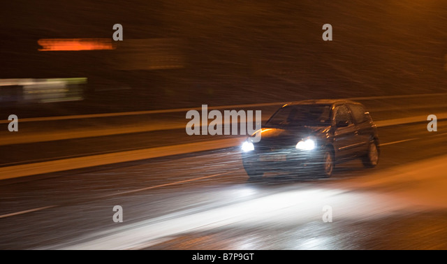 Car driving at night in winter snowing conditions Cwmbran Wales UK - Stock Image
