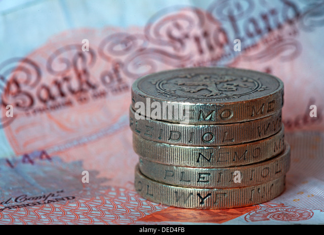 British Sterling Pound coins stacked spelling 'Money' sitting on a UK £10 note - Stock Image