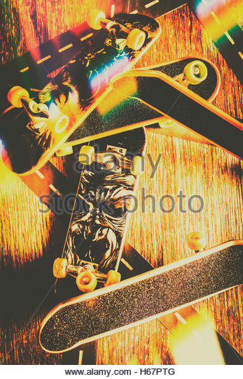 Retro 80's design on a pile of toy skateboards layered with revival colour flares. Skateboarding tricks and - Stock Image