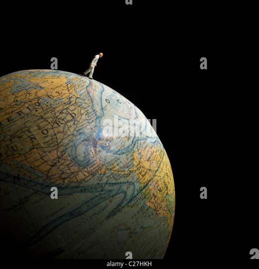 Businessman figurine on globe - global trade / discovery / new markets / export concept. - Stock Image