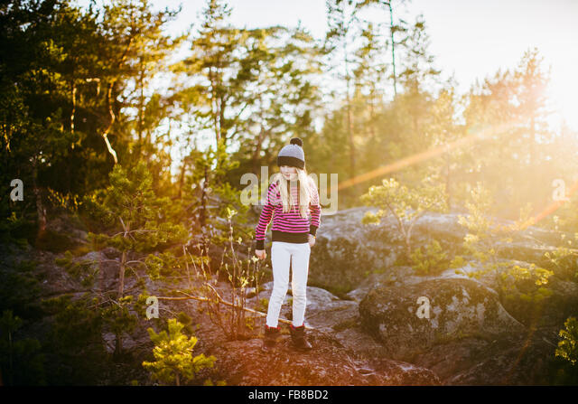 Sweden, Medelpad, Sundsvall, Juniskar, Portrait of girl (10-11) standing in forest on sunny day - Stock Image