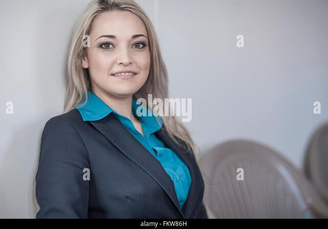 Portrait of young businesswoman with long blond hair sitting in office - Stock Image