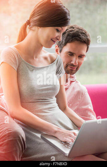 Couple relaxing together on sofa with laptop computer - Stock Image