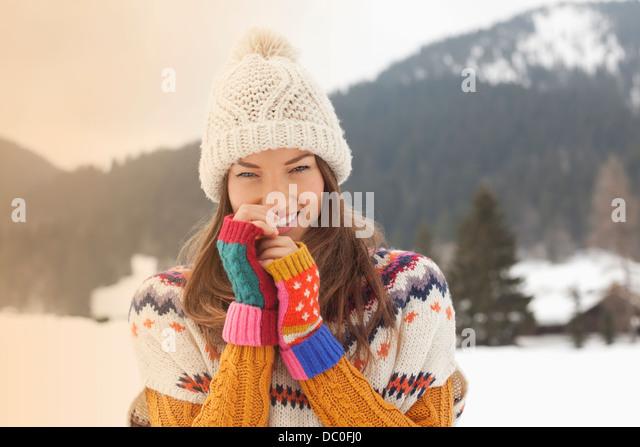 Portrait of smiling woman wearing knit hat in snowy field - Stock Image