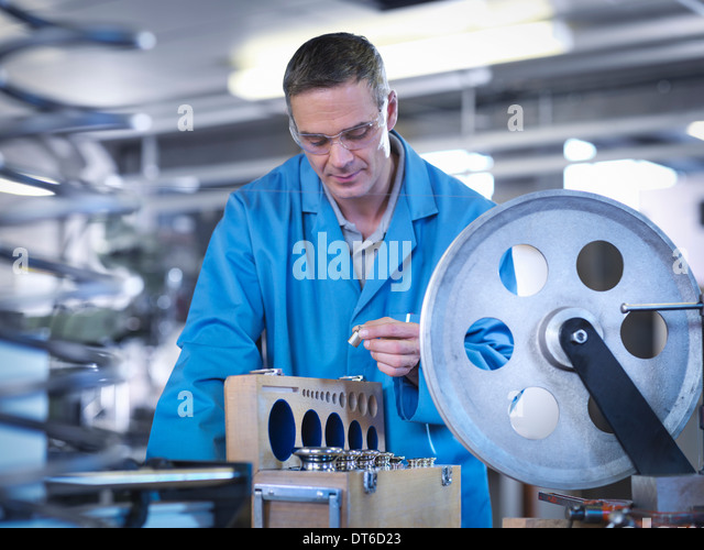 Worker calibrating equipment for automotive use - Stock Image