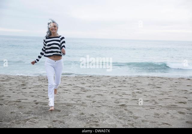 Mature woman running on beach, Los Angeles, California, USA - Stock Image