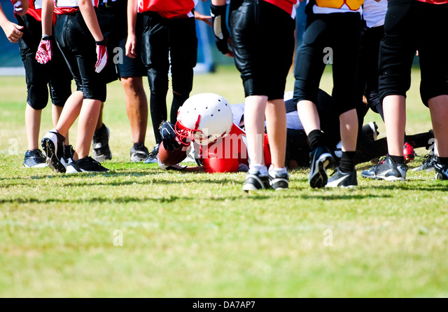 Tackled football boy in the middle of a group of players. - Stock Image