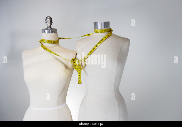 Tape measure tied around tailors dummies - Stock Image