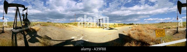 California Mojave CA Oil Rigs donkeys Pumping Oil Cloudy Blue Sky - Stock-Bilder