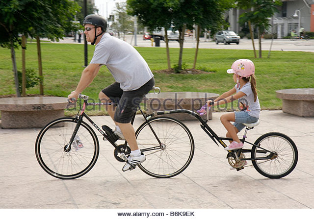Miami Florida Bayfront Park man girl father daughter parent child family tandem bicycle helmet safety physical activity - Stock Image