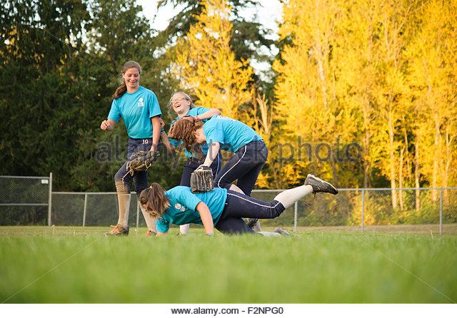 Softball team celebrating on field - Stock-Bilder