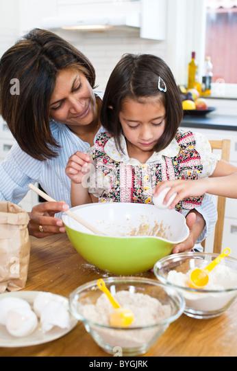 Mother baking with daughter in kitchen - Stock-Bilder