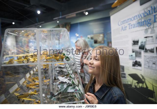 Curious girl looking at airplane model exhibit in war museum - Stock-Bilder
