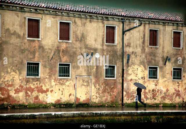 A man carrying and umbrella walks along a terra-cotta building in Venice, Italy - Stock Image