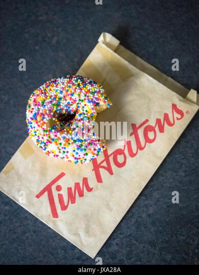 A vanilla dip donut (sprinkle donut, rainbow sprinkle donut) from Tim Hortons, a popular Canadian fast food restaurant - Stock Image